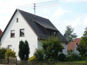 Ein weißes dreistöckiges Haus mit Dachfenster und Steildach