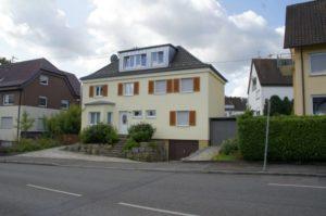 Ein gelbes Haus mit einem schönen Dachfenster und restaurieren Steildach von der Seite