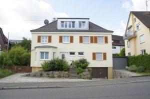 Ein gelbes Haus von vorne mit einem schönen Dachfenster und restaurieren Steildach